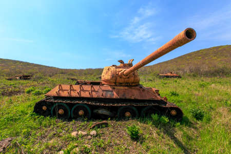 An old rusty tank stands in the middle of thick grass near the seashore. The abandoned battle tank rusted with old age