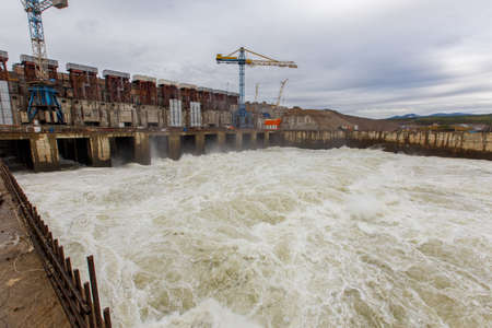 Autumn, 2016 - Magadan, Russia - Construction of the Ust-Srednekanskaya hydroelectric station. A large stream of water coming out from under the river bamboo on the Kolyma river during its construction Standard-Bild