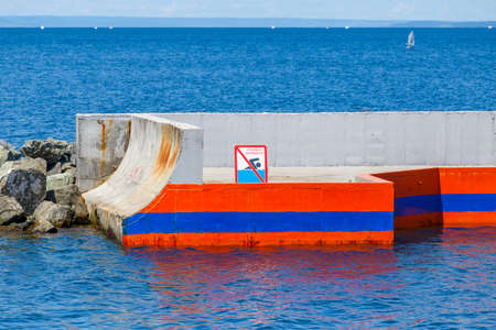 Summer, 2016 - Vladivostok, Russia - Water area of Fedorov Bay in Vladivostok. The No Swimming sign stands at the end of a concrete pier against the backdrop of blue water