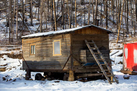 Wooden houses on the logging site in winter. Wooden technical and residential buildings in the deep taiga for co-workers of the timber industry complex