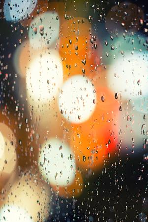 Raindrops on glass at night photo