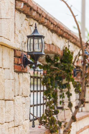 reachability: Stone fence with wrought-iron grille and lights  in classic style