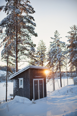 log cabin winter: Small log cabin behind vaporing river in winter in Lapland, Finland