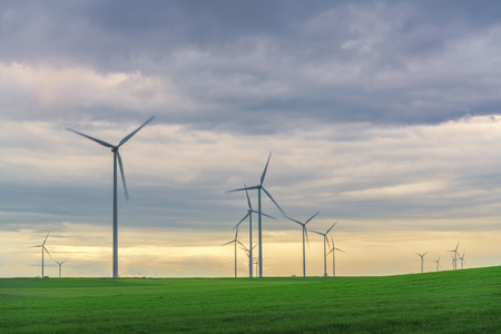 A wind farm of wind turbines creating green energy. Wind turbines clean energy, protection of nature