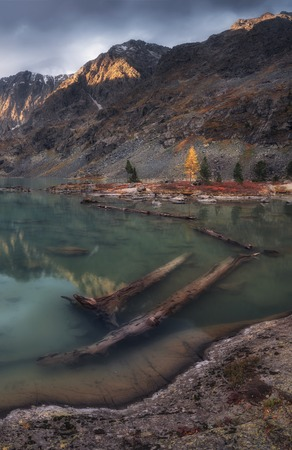 Blue Muddy Water Lake Surrounded By Mountains Reflecting The Sky, Altai Mountains Highland Nature Autumn Landscape Photo. Beautiful Russian Wilderness Scenery Image. Stock Photo