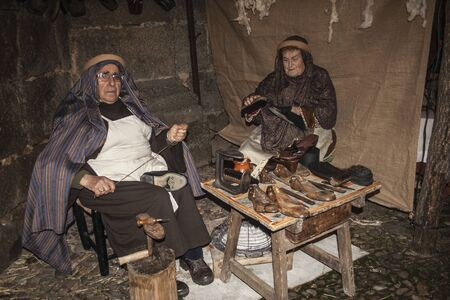 Living Bethlehem Christmas 2012, Navamorcuende, Toledo, SpainCobbler, craftsman, shoes, work shoemaker, sandals, albarcas Editorial