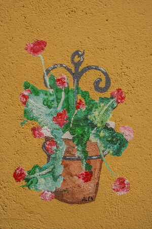 Painted pot of geraniums on a facade