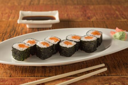 Eight pieces of salmon sushi on a plate with chopsticks and soy sauce 版權商用圖片