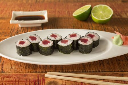 Eight pieces of tuna sushi on a plate with chopsticks and soy sauce