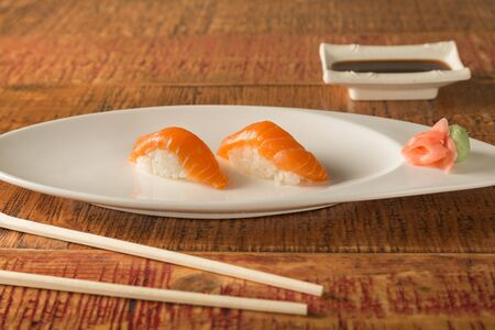 two pieces of salmon sashimi sushi on a plate with chopsticks and soy sauce