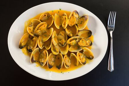 Clams cooked in sauce on a plate on a table 版權商用圖片