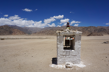 mantra: Mantra object and sculpture at the center of a way to the mountain Leh Ladakh India Stock Photo