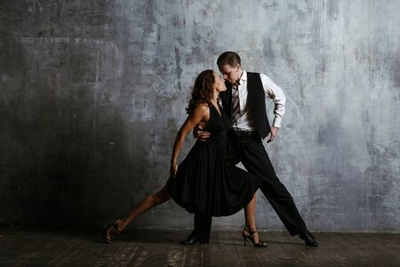 Young pretty woman in black dress and man dance tango Stok Fotoğraf - 99150022