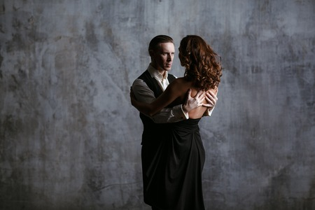 Young pretty woman in black dress and man dance valse Stok Fotoğraf