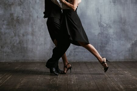 Young pretty woman in black dress and man dance tango 스톡 콘텐츠