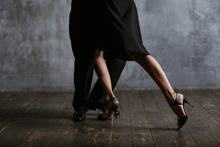 Young pretty woman in black dress and man dance tango Stockfoto