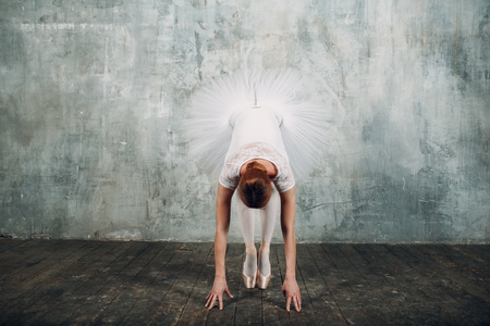 Ballerina bows. Young beautiful woman ballet dancer, dressed in professional outfit, pointe shoes and white tutu.