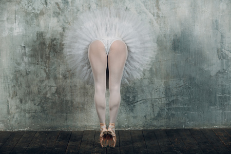 Ballerina legs. Beautiful woman ballet dancer, dressed pointe shoes and white round tutu.in ballroom.
