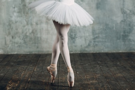 Ballerina in ballroom. Young beautiful woman ballet dancer, legs and pointe shoes and white tutu.
