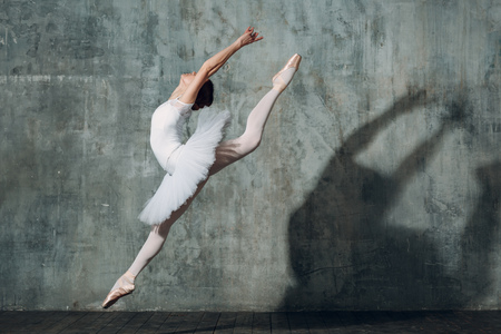 Jumping ballerina . Young beautiful woman ballet dancer, dressed in professional outfit, pointe shoes and white tutu.