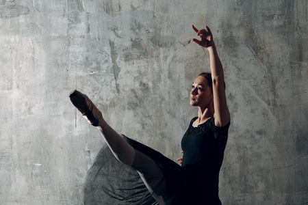 Ballerina in black. Young beautiful woman ballet dancer, dressed in professional outfit, pointe shoes and black skirt.