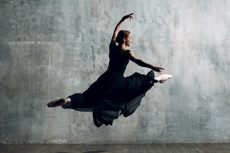 Ballerina jump. Young beautiful woman ballet dancer, dressed in professional outfit, pointe shoes and black dress.