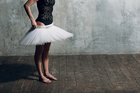 Ballerina putting on white tutu. Young beautiful woman ballet dancer,