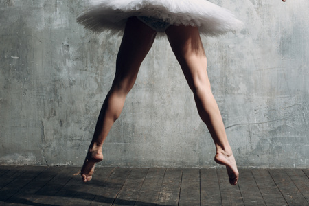 Ballerina slim legs. Young beautiful woman ballet dancer, dressed in professional outfit, pointe shoes and white tutu.