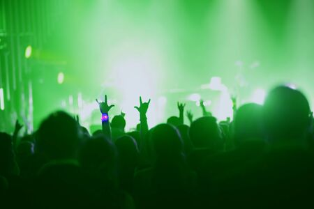 Concert, event or party concept. People with hands up at scene, spotlight, colored green light.