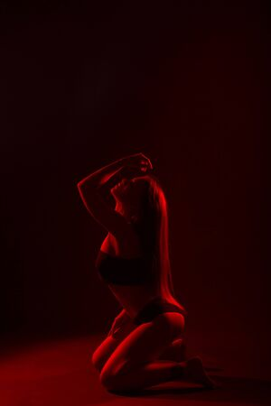 Young beautiful woman in lingerie posing in red back light