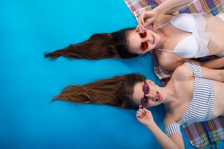 Young two woman lay sunbathe mat in white swimsuit lingerie with funny hairstyle isolated on blue background