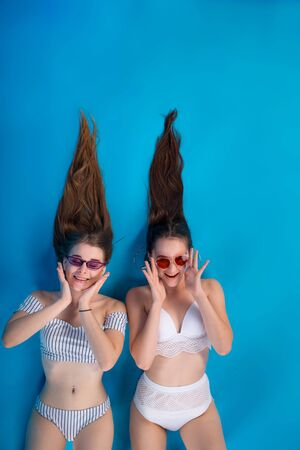 Young two woman sunbathe in white swimsuit lingerie with funny long hairstyle isolated on blue background