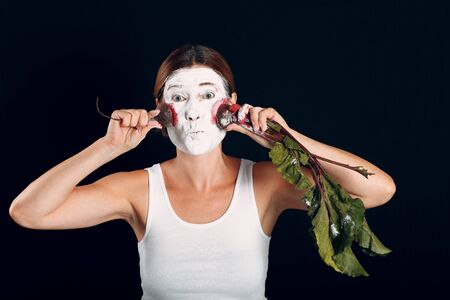 Young woman applying make-up, paints face with red  beet and makeup. How not to do make up concept. Stok Fotoğraf
