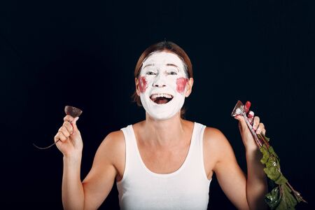 Young woman applying make-up, paints face with beet and makeup. How not to do make up concept.