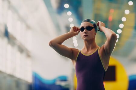 Young woman swimmer getting ready for competition and swim in swimming pool Stok Fotoğraf