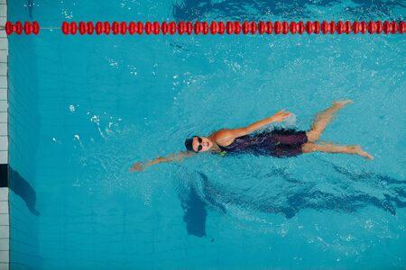 Young woman swimmer swims in swimming pool Stok Fotoğraf