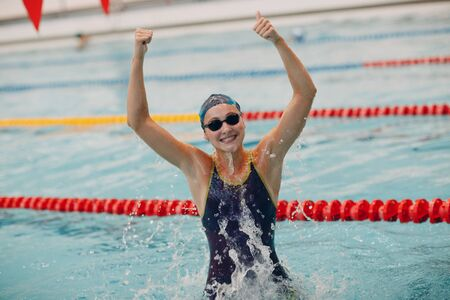 Young woman swimmer portrait joy rejoices in victory in swimming competitions in swimming pool