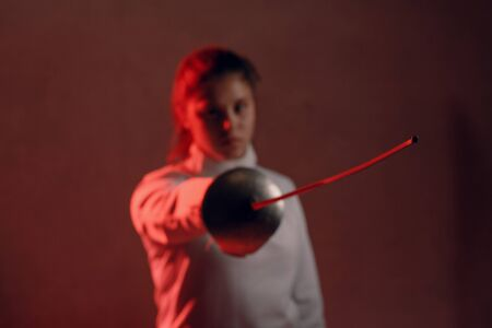 Fencer woman portrait with fencing sword in red light.