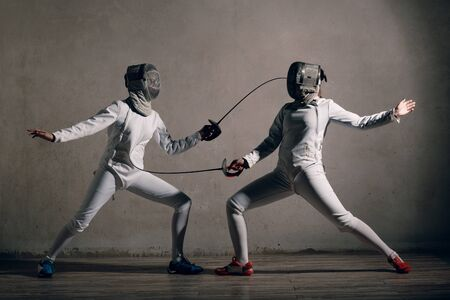 Fencer woman with fencing sword. Fencers duel concept.