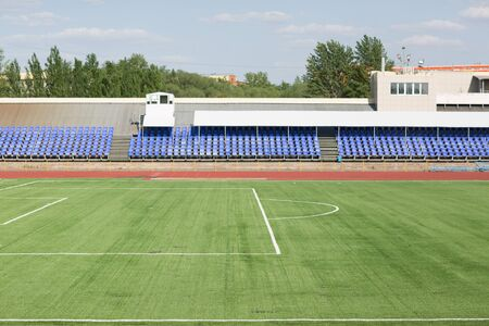 Running track and field with green grass for football at stadium Archivio Fotografico