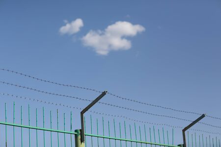 Lonely cloud in blue sky behind barbed wire Banque d'images