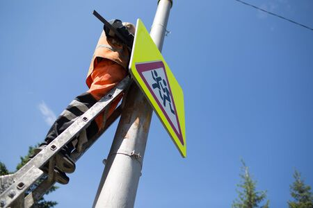 Installation road sign on pole. Road worker sets sign on blue sky background.