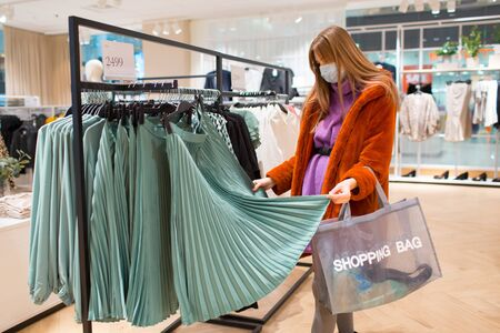Young beautiful woman chooses clothes in store.