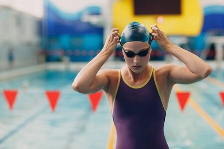 Young woman swimmer prepare to swim in swimming pool