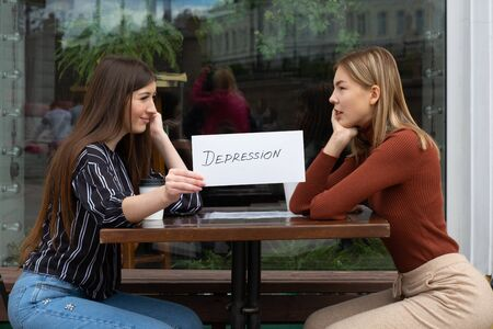 Woman holding white sheet paper labeled word Depression in hand. Two women talking in street cafe. Hidden depression concept