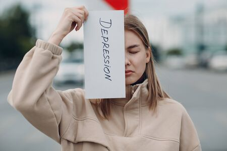 Woman holding white sheet paper labeled word Depression in hand. Banque d'images