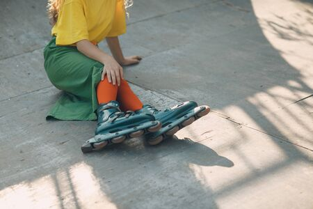 Young woman girl in green and yellow clothes going roller skate