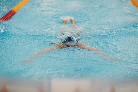 Young woman swimmer swims in swimming pool Banque d'images