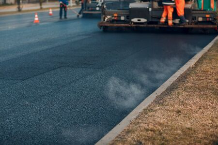 Asphalt paving. Paver machine and road roller. New road construction Stock Photo