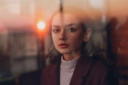 Beautiful young teenager girl portrait behind window glass
